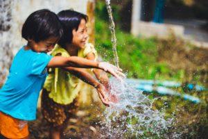SE CONNECTER À SA PETITE VOIX INTÉRIEURE : 2 enfant souriant et riant autour d'un jet d'eau.