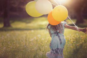 SE CONNECTER À SA PETITE VOIX INTÉRIEURE : femme courant dans un champ avec des ballons de couleur.