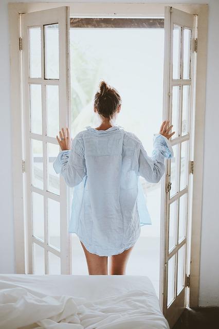 Femme devant une fenêtre ouverte.