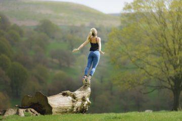 Femme sautant d'un tron d'arbre