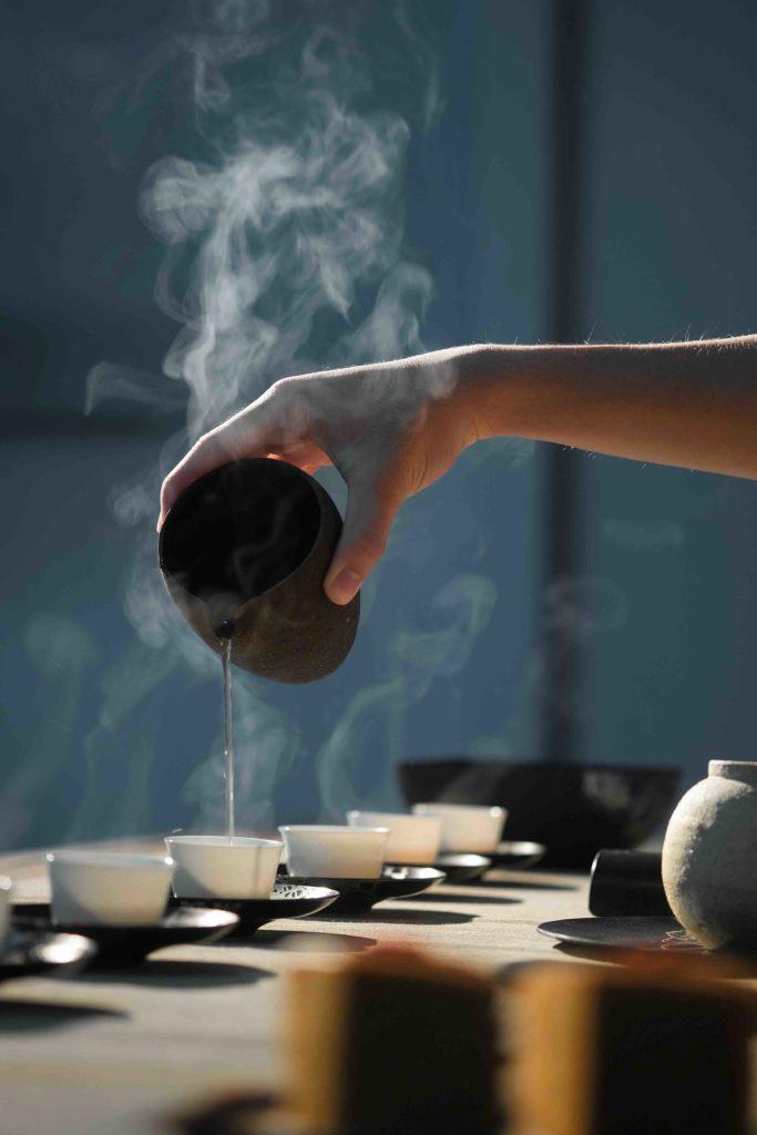 Main versant du thé dans des tasses.