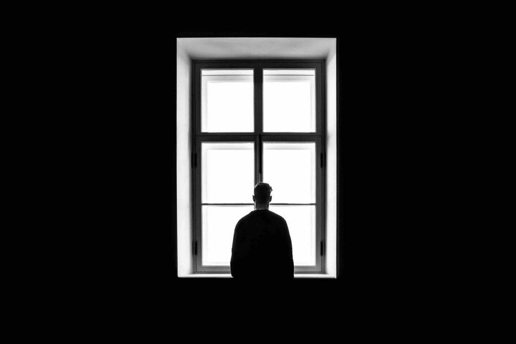 Homme seul face à la fenêtre.