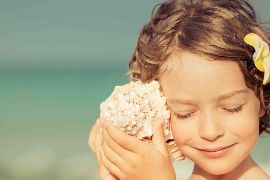 Une petite fille écoute un coquillage collé à son oreille.
