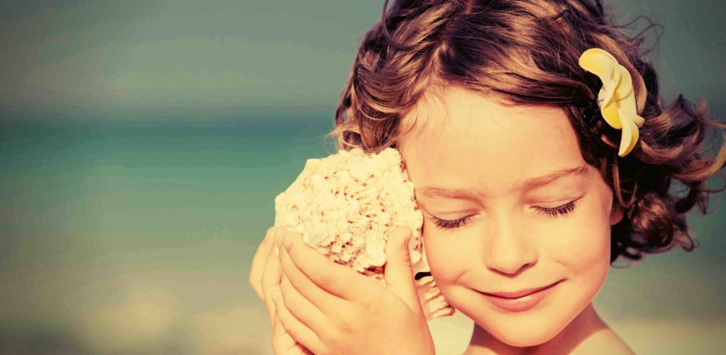 Page à propos du site :  photo d'une petite fille écoutant dans un coquillage.