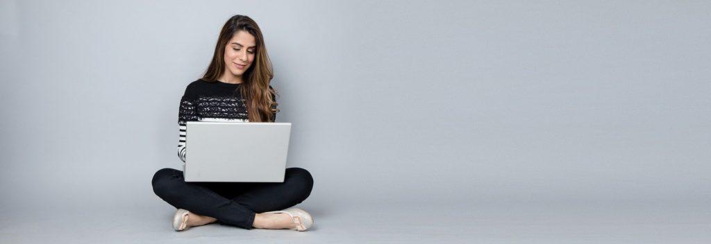Pour être tout à fait Clair.e : jeune femme assise avec ordinateur portable.