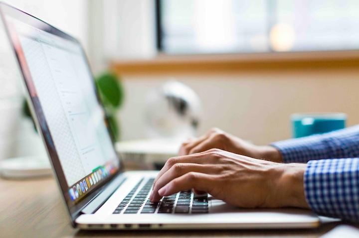 Mains qui tapent un mail sur un ordianteur.