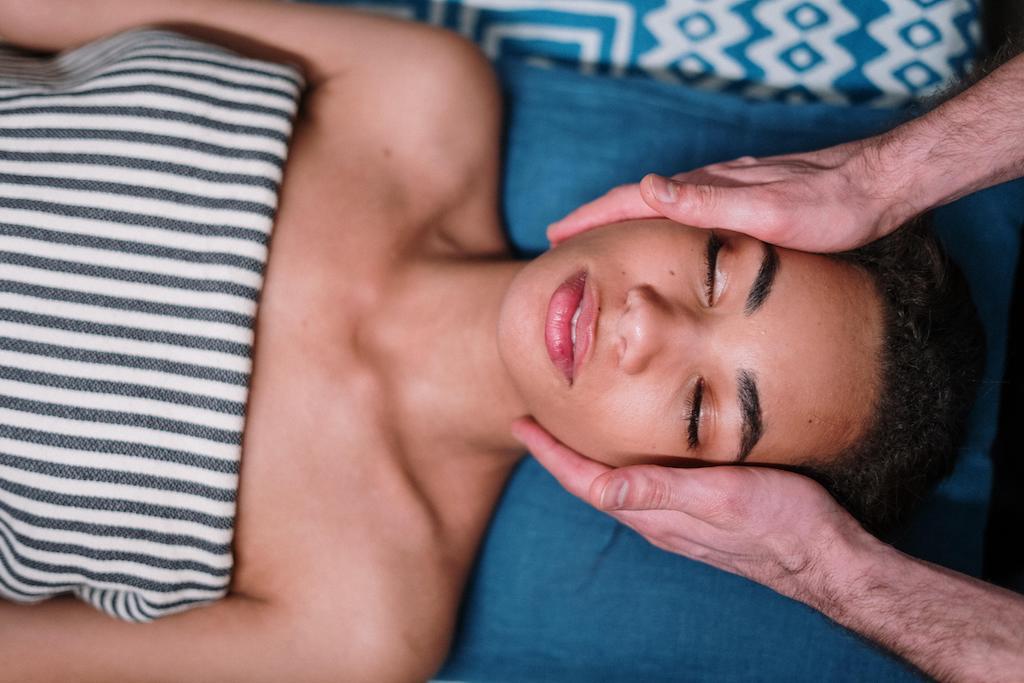 Mains posées sur le visage d'une femme allongée