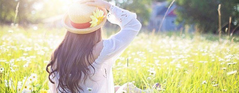 Femme au chapeau assise dans l'herbe